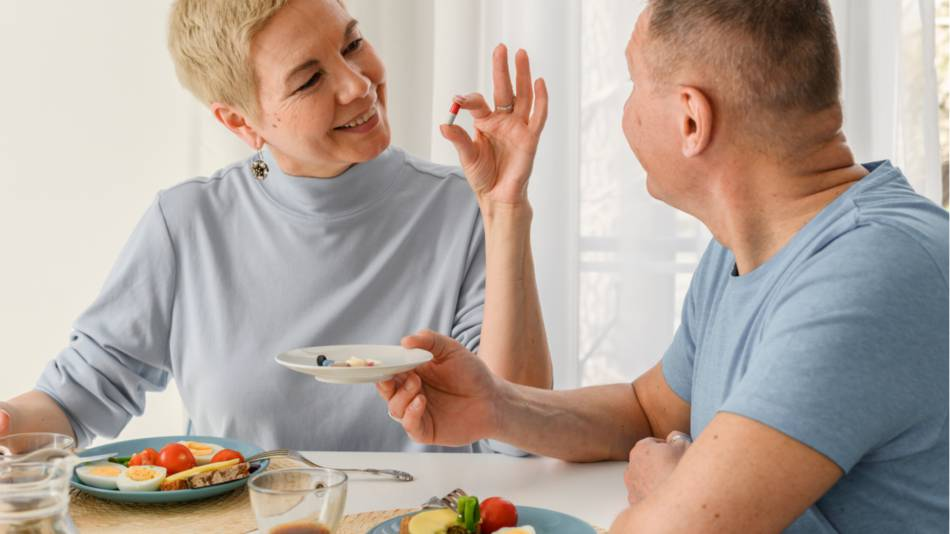 Woman holding a pill and showing it to a man while sitting at a table about to eat a meal