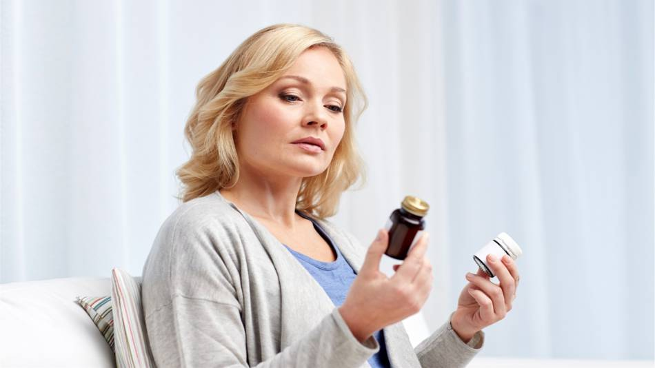 PQQ Supplements and How They Compare With CoQ10 -- woman holding two supplement bottles