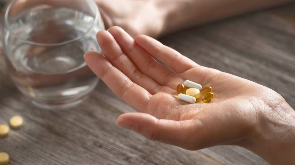 Woman holding various vitamins and supplements in one hand and glass of water in the other
