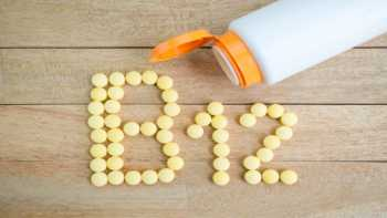 The danger of taking too much vitamin B-12 -- bottle of vitamin B-12 with pills on the table spelling out 'B-12'
