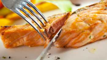 Wild Caught vs. Farm Raised Salmon -- salmon on a dinner plate with fork and knife