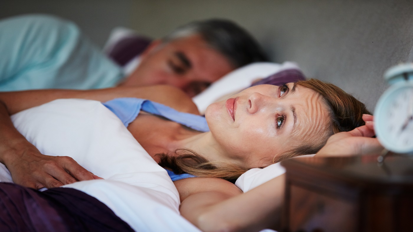 Woman with insomnia awake in bed and having trouble sleeping