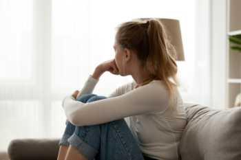 Best Supplements for Depression and Anxiety -- sad young woman sitting on couch, looking toward the window