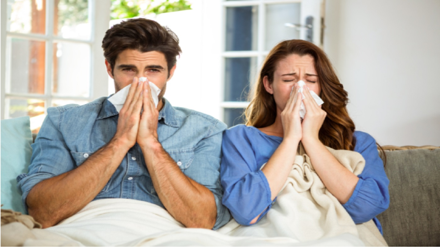 Supplements for Colds: Zinc, Echinacea & More -- Couple with cold, sitting on couch blowing their noses