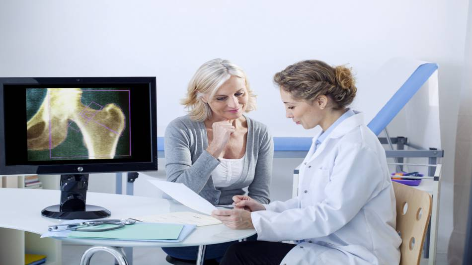 Supplements for Osteoporosis -- Doctor and older woman looking at spinal x-ray