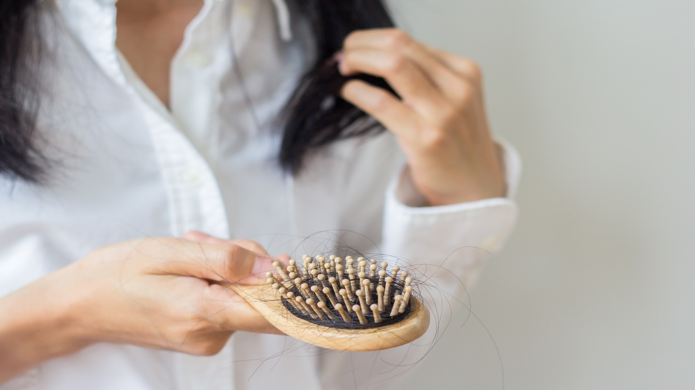 Supplements for Hair Loss -- woman looking at hairbrush
