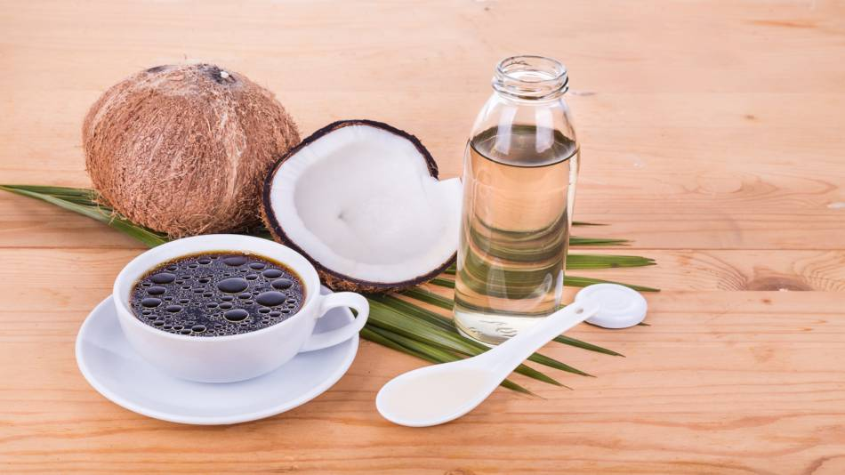 Coconut Oil & MCTs -- Coconuts and coconut oil with coffee cup
