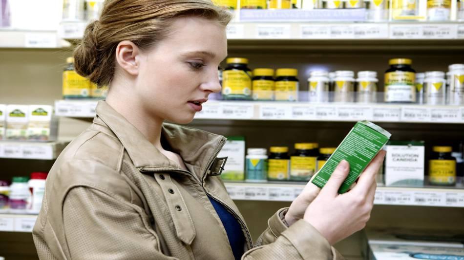 Misleading Supplement Labels -- woman reading supplement label