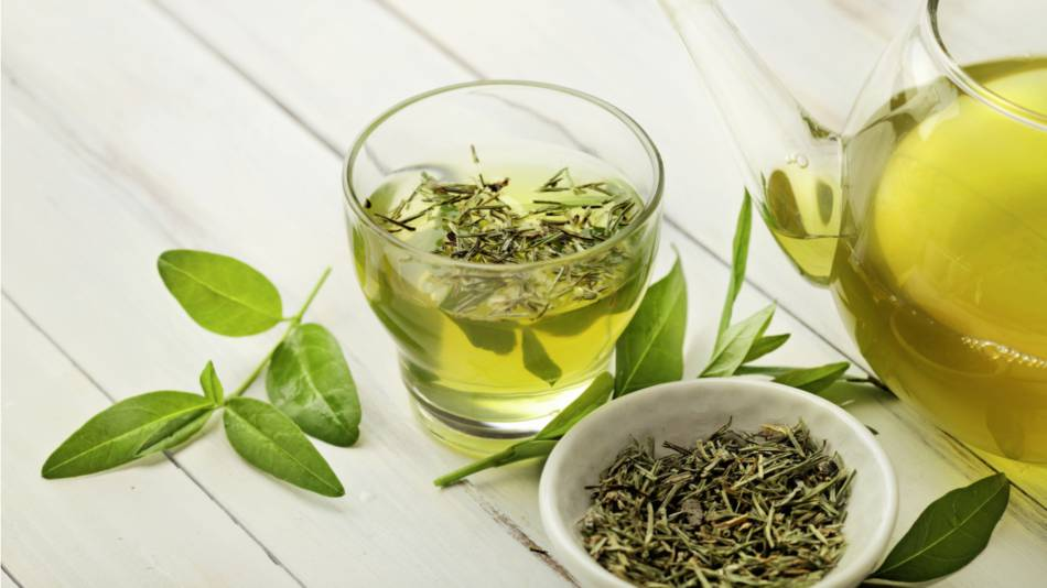 Cup of green tea with dried tea leaves