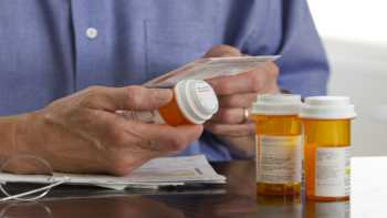 Supplement Interactions With Antibiotics -- man reading prescription bottle instructions