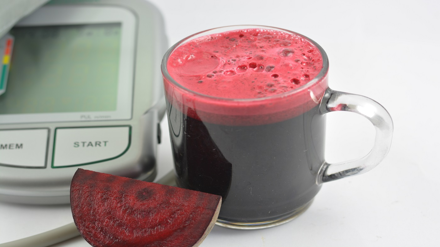 Beetroot Juice for Lowering Blood Pressure? -- Glass of beetroot juice and blood pressure monitor
