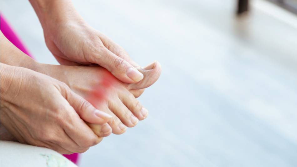 Woman with gout pain rubbing her foot near the big toe