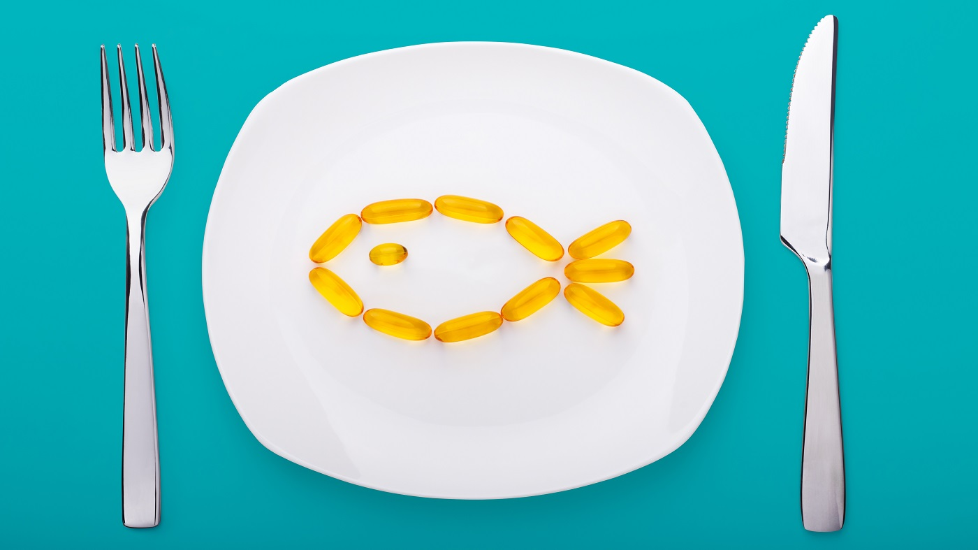 Best Way to Take Fish Oil -- fish oil capsules on plate with fork and knife