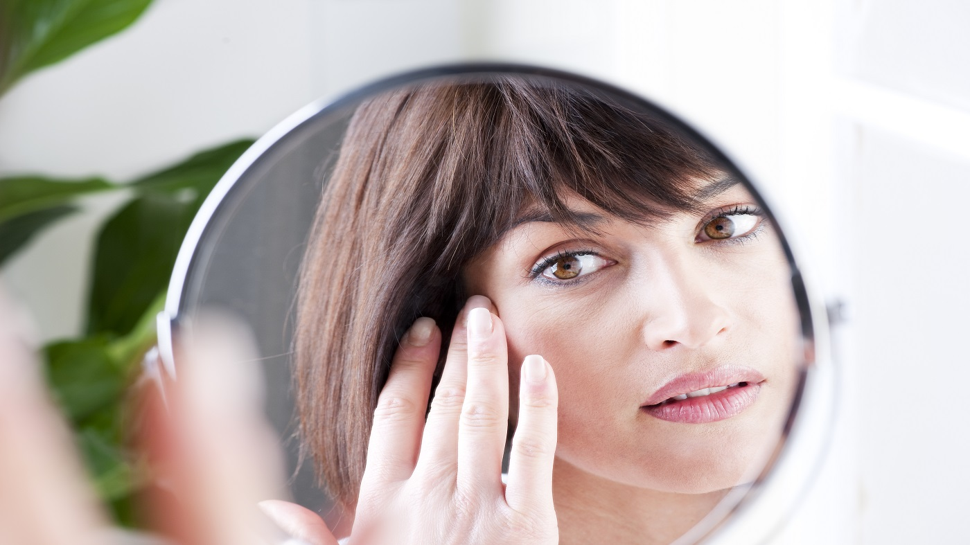 Collagen Supplements for Wrinkles? -- woman looking closely at her face in a mirror