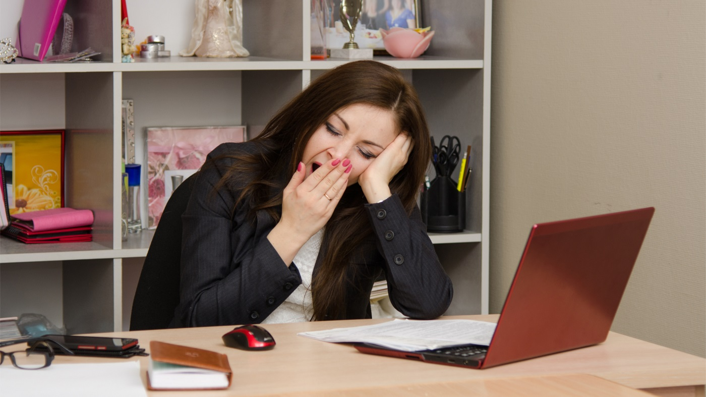 Supplements to Improve Energy and Decrease Fatigue -- tired woman yawning at desk