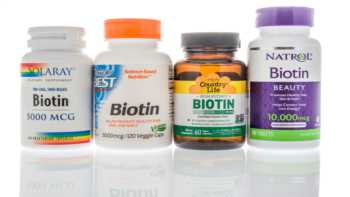 Biotin Supplements for Hair and Nails -- woman looking at hair and nails in mirror
