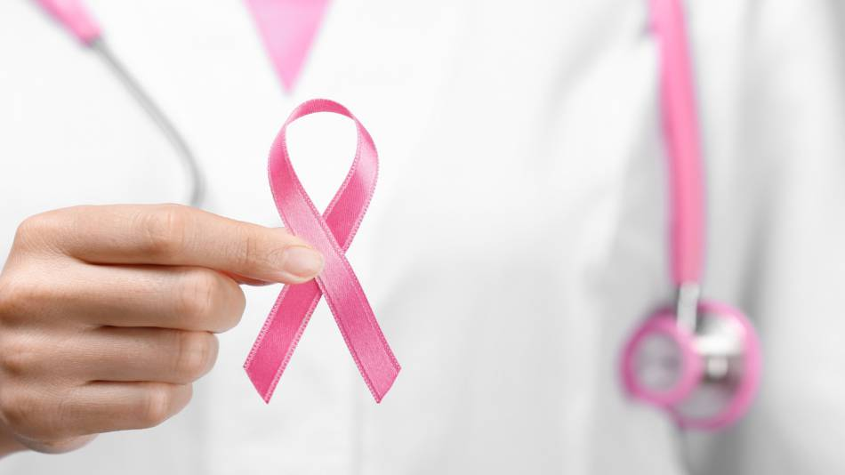 Supplements & Breast Cancer Risk -- doctor holding pink breast cancer awareness ribbon