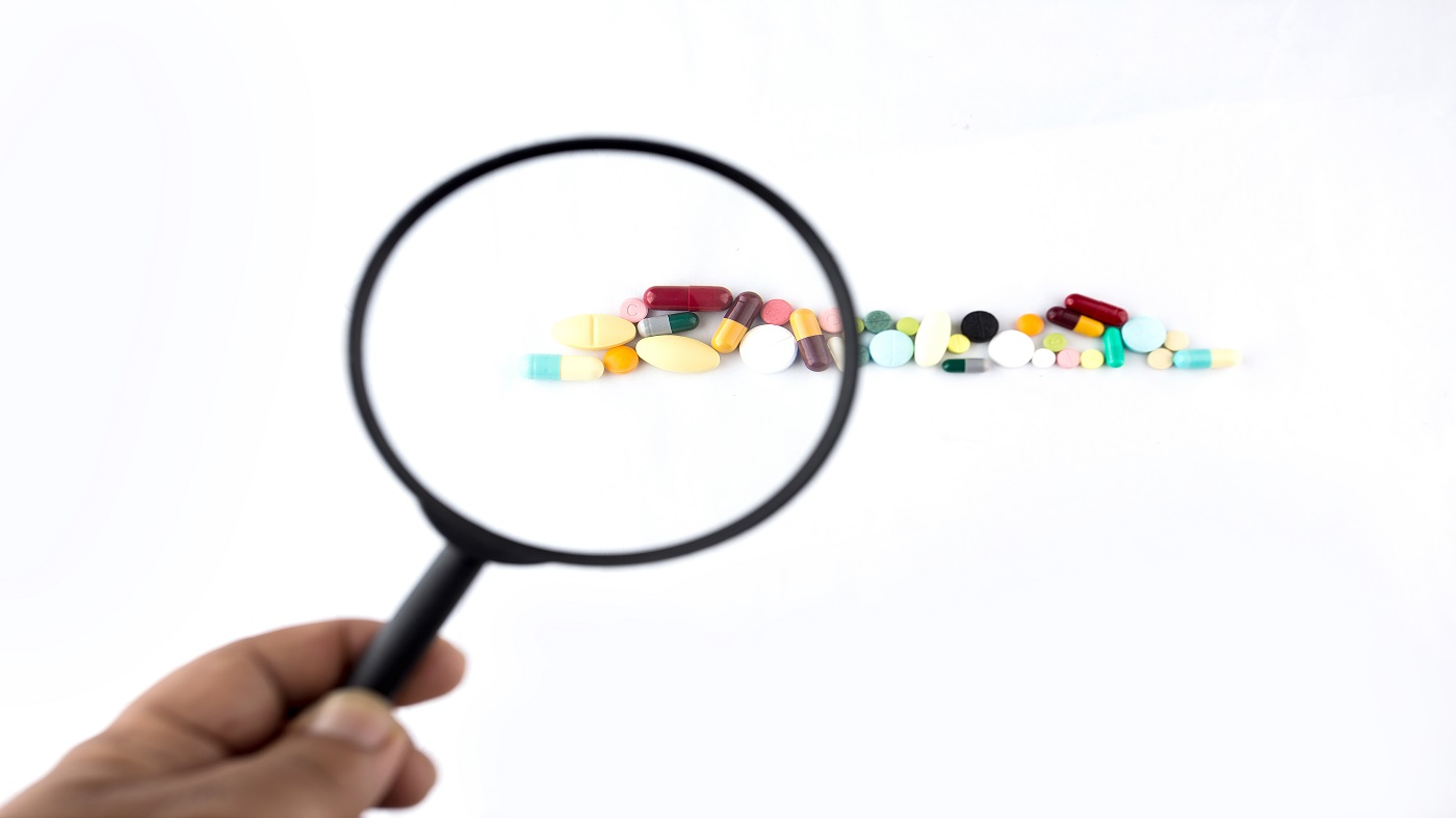 Multivitamins with 100% Daily Requirements -- magnifying glass held over multivitamin pills