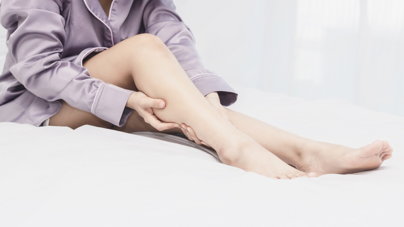 Woman in bed with leg cramp