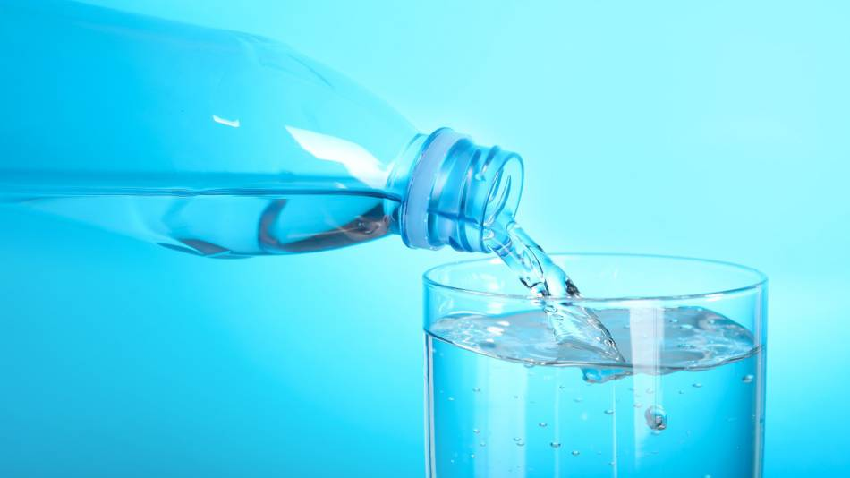 Microplastics in water, plastic bottle of water pouring water into glass
