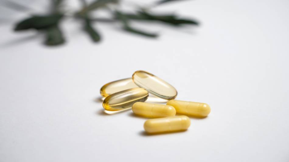 hand holding vitamin D and fish oil capsules
