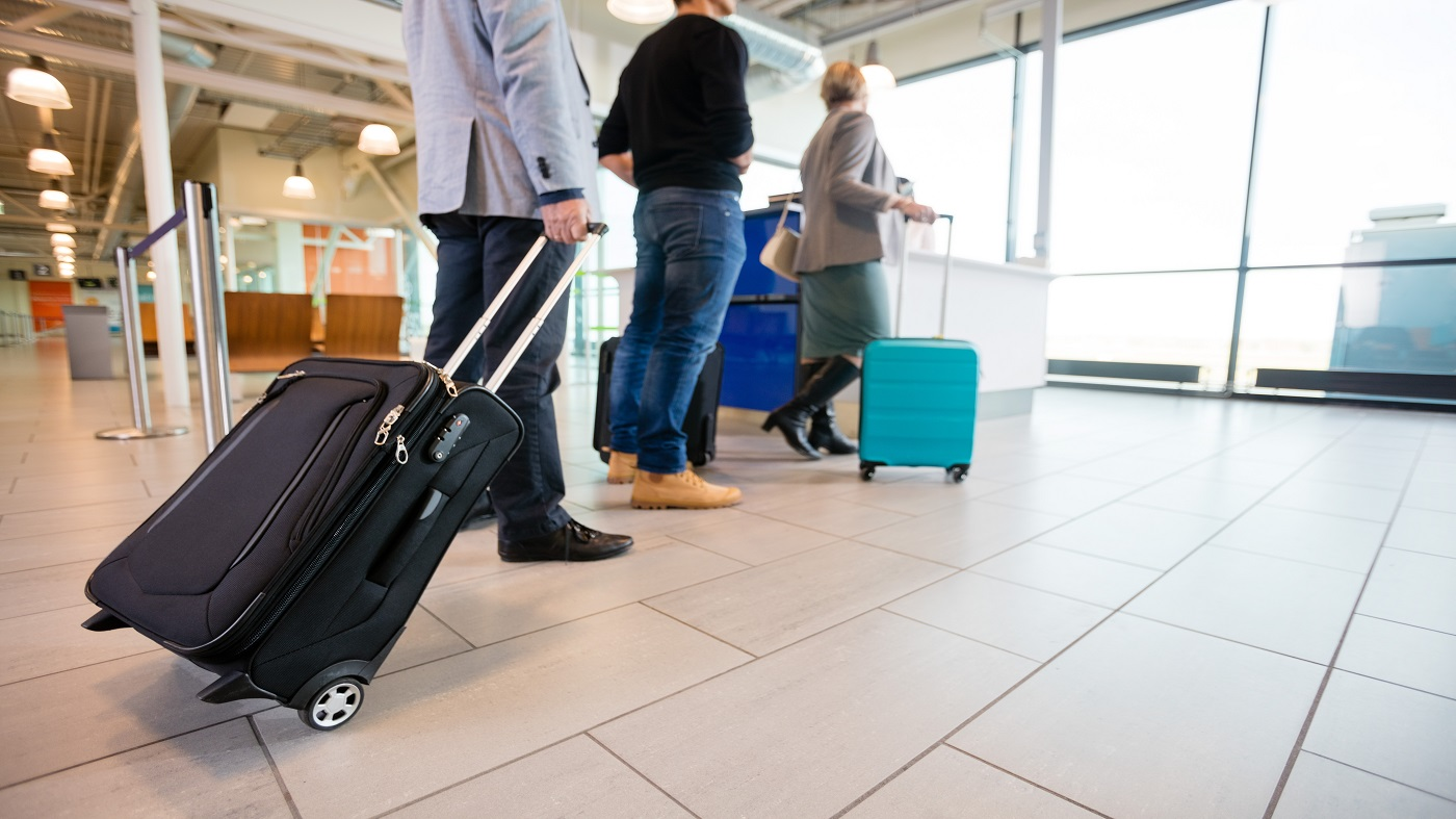 Is it legal to take CBD on a flight? -- men and women with baggage standing in line at the airport