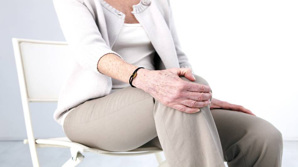 Curcumin and Boswellia for Knee Pain -- Older woman with osteoarthritis holding knee in pain