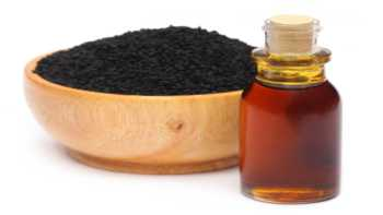 Black seed oil benefits -- bowl of black cumin seeds and bottle of oil