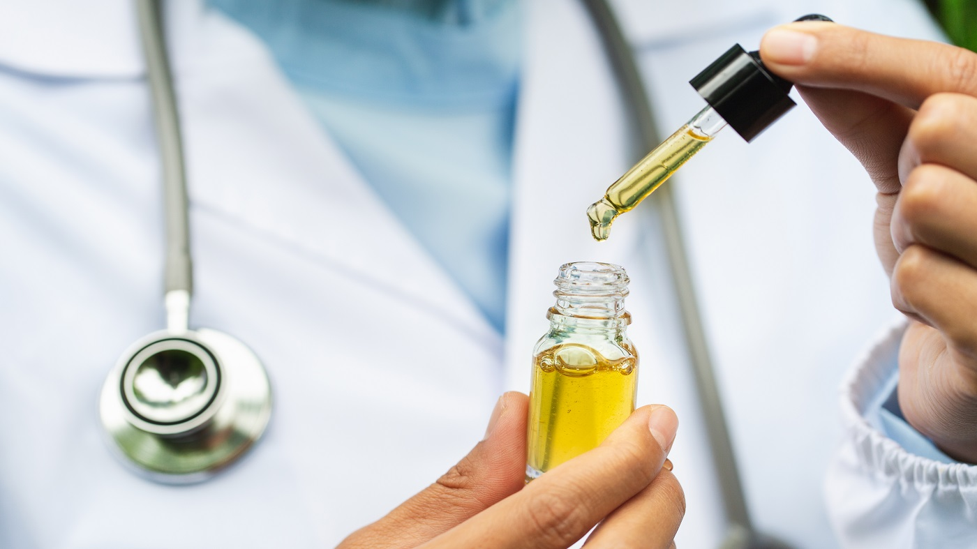 CBD (cannabidiol) drug interactions -- doctor holding bottle of CBD oil