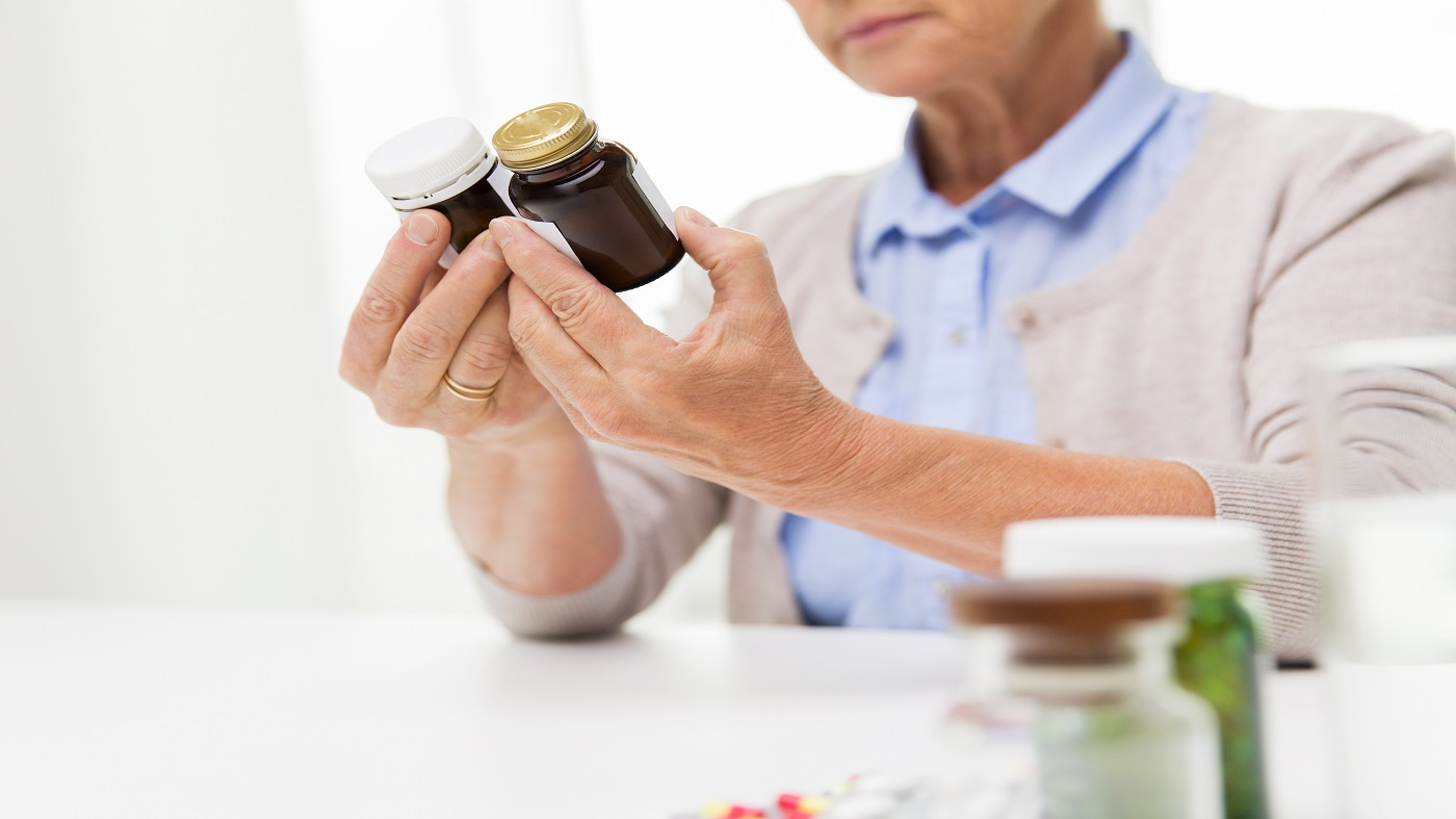How to compare supplement labels -- woman looking at the labels of two supplement bottles