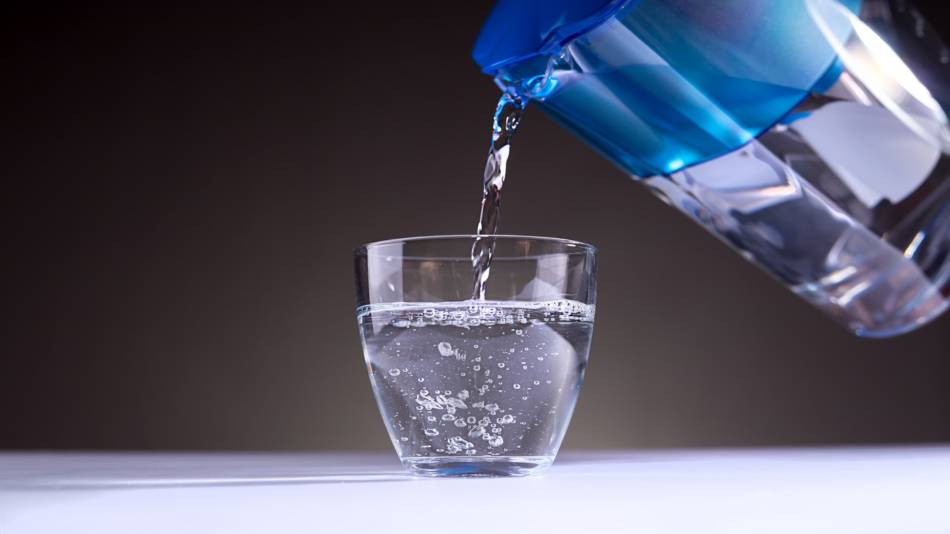 Water Filters for Microplastics -- water filter pitcher pouring water into glass