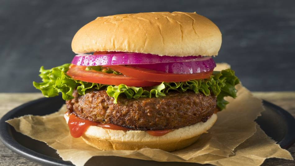 Beyond Burger vs. Impossible Burger: Nutrition, Vitamins & Minerals -- cooked plant-based burger on bun