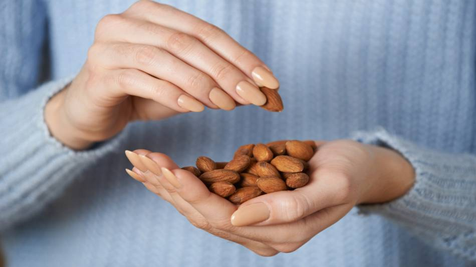 Eating Almonds to Reduce Wrinkles? -- woman with handful of almonds