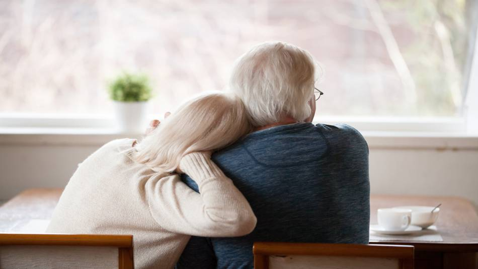 Staying Healthy During the Coronavirus Pandemic -- Couple at Home, Looking Out the Window