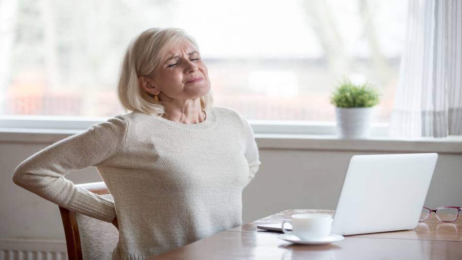 Chuchuhuasi for Inflammation & Back Pain? -- Woman With Back Pain Sitting, at Desk Drinking Tea