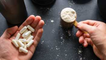 Hands holding essential amino acid capsules and protein powder