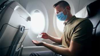 Is it safe to fly and how can I avoid getting COVID-19? -- Man on Airplane With Mask and Hand sanitizer