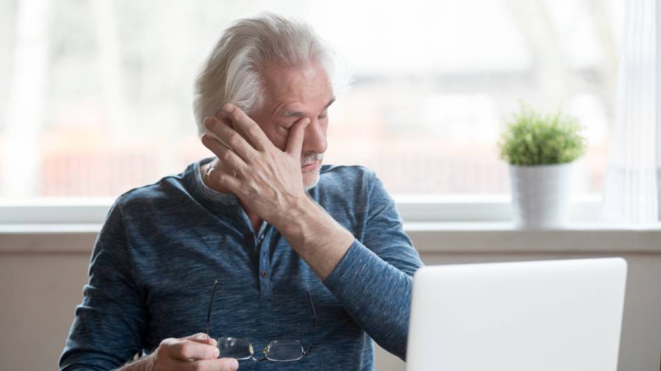 Older man with dry eye rubbing his eyes while holding his glasses