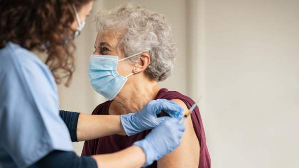 Older woman with mask who is about to receive COVID-19 vaccine