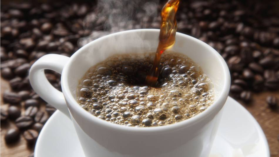 Coffee being poured into white coffee cup