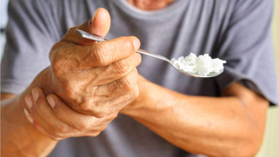 Elderly man with parkinsons holding trembling hand while eating