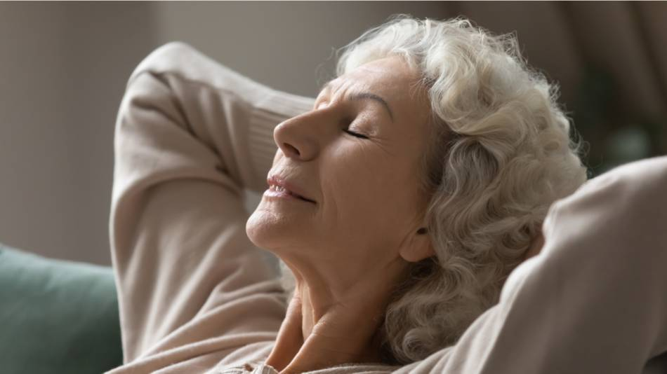 Older women sitting calmly on a couch with her hands behind her head and her eyes closed