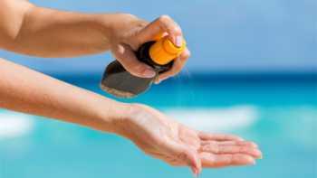 Benzene in Suncreen -- Spraying Sunscreen Onto Hand on the Beach