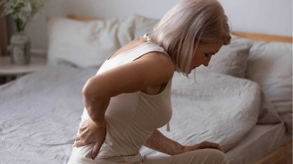 Older woman with multiple sclerosis who is experiencing back pain while sitting on her bed