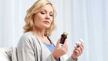 Woman with NSAID-hypersensitivity looking at two supplement containers and wondering if they are safe to take