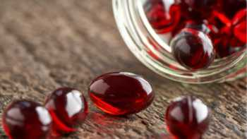 Capsules of astaxanthin being poured onto a wooden table