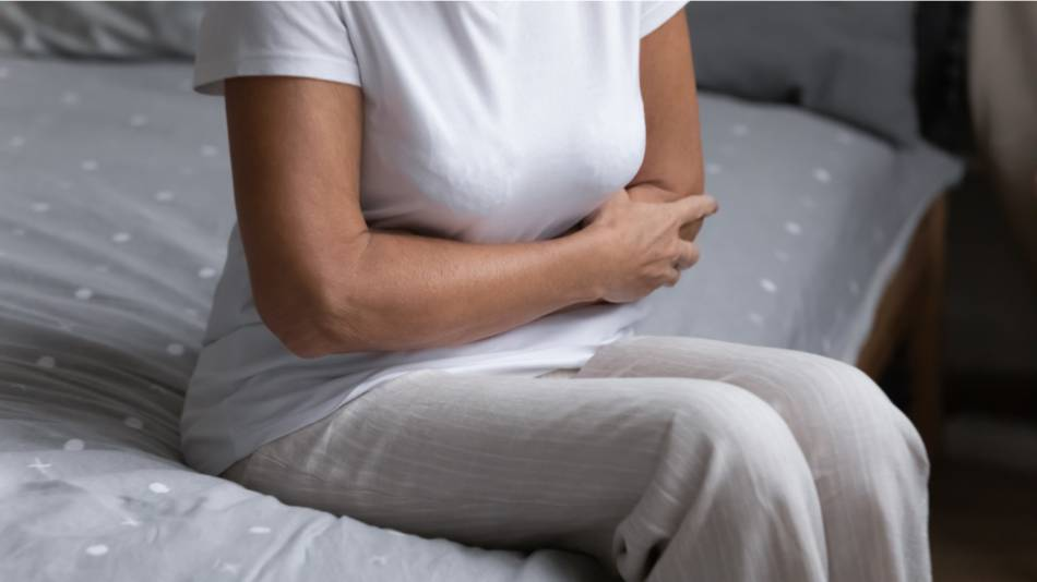 Older woman sitting on her bed and holding her stomach due to gas and bloating