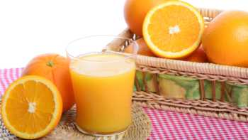 A glass of orange juice sitting on a table and surrounded by sliced and whole oranges