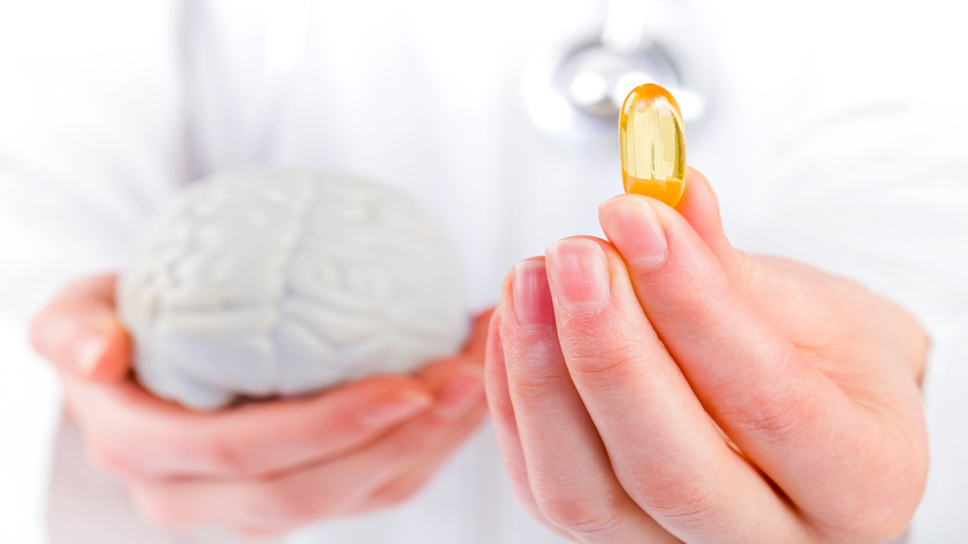 Supplements for Memory -- doctor holding a model of a brain and fish oil capsule